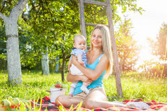 Beautiful mother with baby sitting outdoors on a blanket Royalty Free Stock Photo