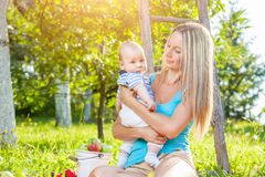 Beautiful mother with baby sitting outdoors on a blanket Royalty Free Stock Images