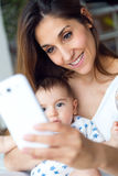 Beautiful mother and baby taking a selfie at home. Stock Image