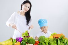 Beautiful mother and boy make salad. Beautiful young mother and little boy make salad with table full of vegetables Royalty Free Stock Images