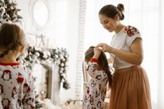Beautiful mother braids her little daughter`s braid in the light cozy room with wonderful  New Year`s tree royalty free stock photo