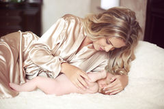 Beautiful mother calm baby lying on bed. Mom hugging her daughte Royalty Free Stock Photo