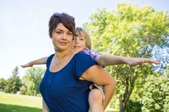 Beautiful Mother Carrying Son On Back At Park Stock Image