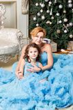 Beautiful mother and charming daughter, sitting near to a Christmas tree and Christmas balls in blue dress.  Royalty Free Stock Images