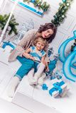 Beautiful mother and charming daughter, sitting next to a Christ. Mas tree and Christmas balls in warm stylish sweater and jeans, with depth of field Photo Royalty Free Stock Photos
