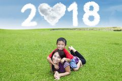 Beautiful mother with child in the meadow. Beautiful women and her son playing in the meadow with clouds shaped heart and numbers 2018 in the sky royalty free stock image