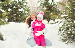 Beautiful mother with child in snowy winter day. On snow Stock Photos