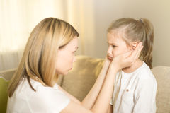 Beautiful mother is comforting his young frustrated daughter. Royalty Free Stock Image