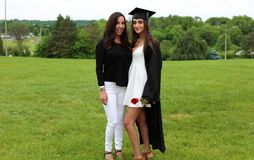 Beautiful mother and daughter in black Cap, Gown and Tass, teenager. Unique gorgeous face, nice smile, wonderful eyes girl. Beautiful mother and daughter in stock photo