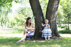Beautiful mother and daughter blow bubbles Royalty Free Stock Photo