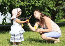 Beautiful mother and daughter blow bubbles Royalty Free Stock Images
