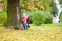 Beautiful mother and daughter close to the tree Stock Image