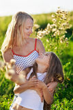 Beautiful mother and daughter family on meadow Stock Images
