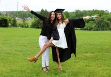 Beautiful mother and daughter in black Cap, Gown and Tass, teenager. Unique gorgeous face, nice smile, wonderful eyes girl. Beautiful mother and daughter in stock photography