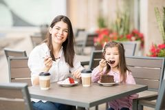 Beautiful mother and daughter having cake at cafe Stock Photography