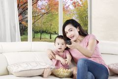 Mother and daughter watching tv with popcorn Royalty Free Stock Photos