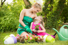 Beautiful mother and daughter planting flowers Stock Photos