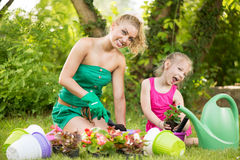 Beautiful mother and daughter planting flowers Stock Images