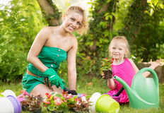 Beautiful mother and daughter planting flowers Stock Photo