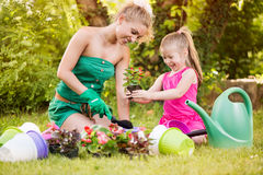Beautiful mother and daughter planting flowers Stock Image