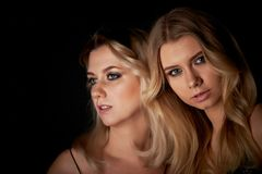 Beautiful mother and daughter portrait in Studio on black background.Look great. Professional makeup royalty free stock photo
