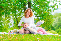 Beautiful mother and daughter resting in a park Royalty Free Stock Image