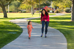 Beautiful mother and daughter running in the neighborhood Stock Photos