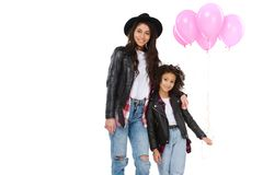 Beautiful mother and daughter in similar clothes with pink balloons. Isolated on white royalty free stock images