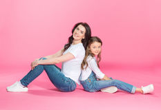 Beautiful mother and daughter sitting back to back and smiling at camera Royalty Free Stock Images