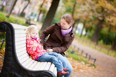 Beautiful mother and daughter sitting on a bench Royalty Free Stock Photo