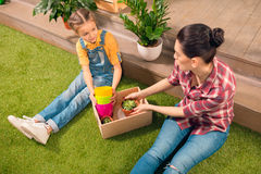 Beautiful mother and daughter sitting on lawn with pots and potted plants Stock Images