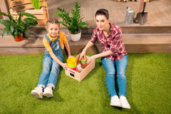 Beautiful mother and daughter sitting on lawn with pots and potted plants Stock Image