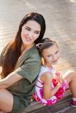 Beautiful mother and daughter sitting outdoors on steps and laughting Royalty Free Stock Photography