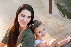 Beautiful mother and daughter sitting outdoors on steps and smiling Royalty Free Stock Image