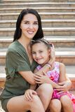 Beautiful mother and daughter sitting on stairs Stock Photography