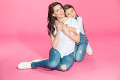 Beautiful mother and daughter sitting together and hugging on pink Stock Photos
