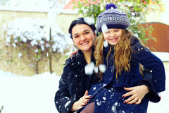 Beautiful mother and daughter smiling. winter snow Royalty Free Stock Images