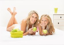 Beautiful mother and daughter together with apple Royalty Free Stock Photography