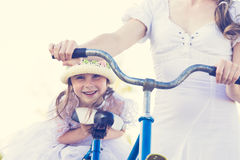 Beautiful mother and daughter traveling on a bicycle. Royalty Free Stock Photos