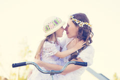 Beautiful mother and daughter traveling on a bicycle. Stock Images