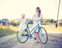 Beautiful mother and daughter traveling on a bicycle. Stock Photo