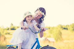 Beautiful mother and daughter traveling on a bicycle. Royalty Free Stock Images