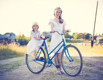 Beautiful mother and daughter traveling on a bicycle. Royalty Free Stock Photography