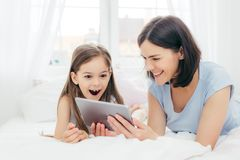 Beautiful mother and daughter watch something funny on tablet computer, connected to wireless internet, spend free time in bedroom stock photos