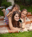 Beautiful mother and daughters making photos on picnic Stock Images