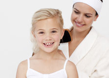 Beautiful mother doing daughter's hair Stock Photo