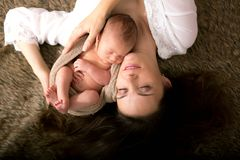Beautiful mother embracing with tenderness and care her newborn Royalty Free Stock Photo