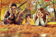 Autumn family picnic. Beautiful mother, father and daughter having fun on an autumn picnic in park; family enjoying sunny autumn day in nature royalty free stock photography