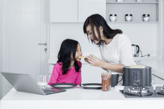 Beautiful mother feed daughter in the kitchen Stock Images
