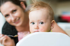 Beautiful mother feeding her baby daughter with yogurt Stock Photos